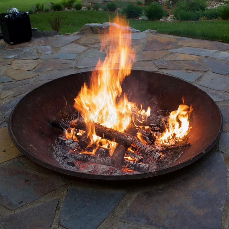 Garden Fire Pit At Sunset. Man made upscale garden fire pit on a warm summer evening royalty free stock photos