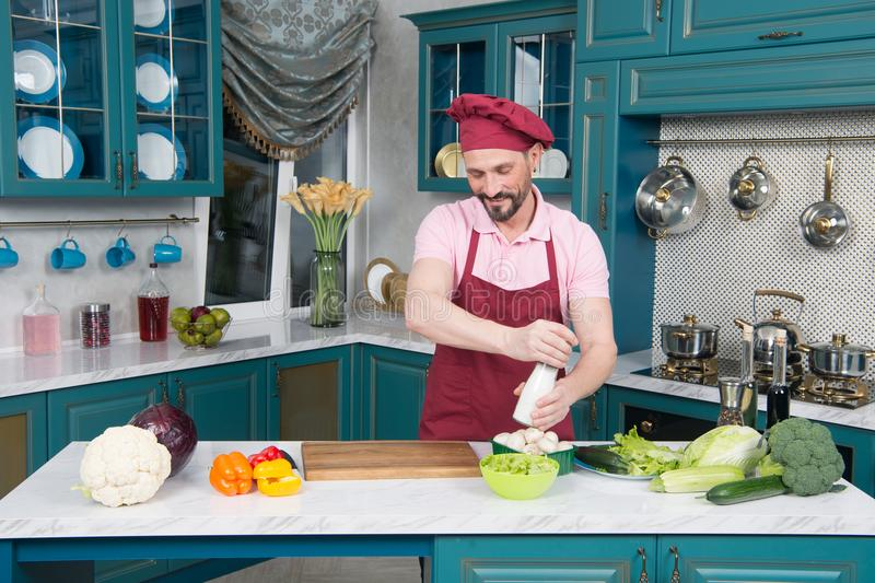 Man made vegetables and salting them. Bearded guy on kitchen cooking. Guy salting salad before serving. Man made vegetables and salting them. Happy chef hold royalty free stock photos