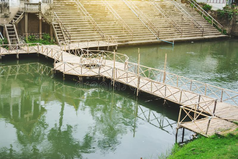 Man made wooden bridge cross small canal. In village royalty free stock photography