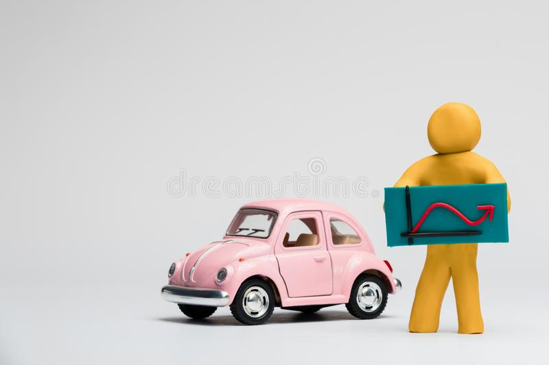 A man made from plasticine holding a graph with an arrow going up and down next to a pink car on white background, aligned to the. A man made from yellow royalty free illustration