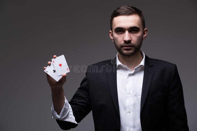 Man magician with two playing cards in his hand over grey background stock photos