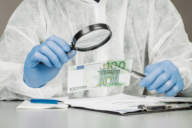 Man with magnifying glass checks suspicious money. Expert with magnifying glass checks suspicious money stock image