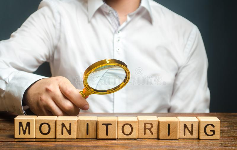 A man with a magnifying glass examines word Monitoring. Verification and control, business audit. Inspector controls the quality. Of products or work stock photo