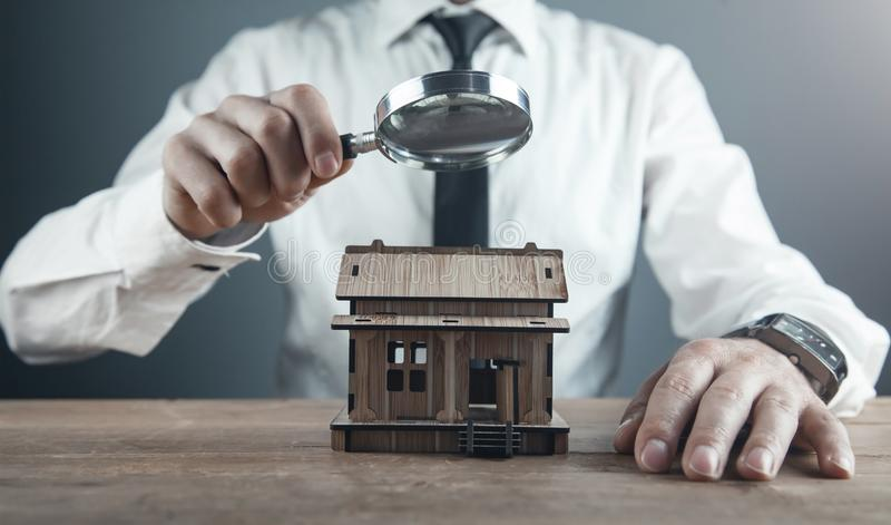 Man magnifying wooden house model. Home inspection royalty free stock photography