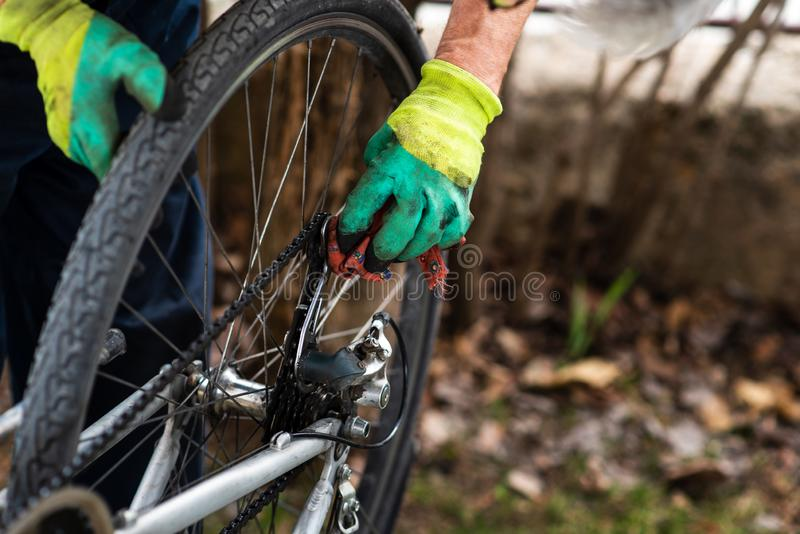 Man maintaining his bicycle for the new season. Man maintaining his bicycle for the new driving season, clean, cleaning, male, drive, fix, fixing, maintenance stock photo