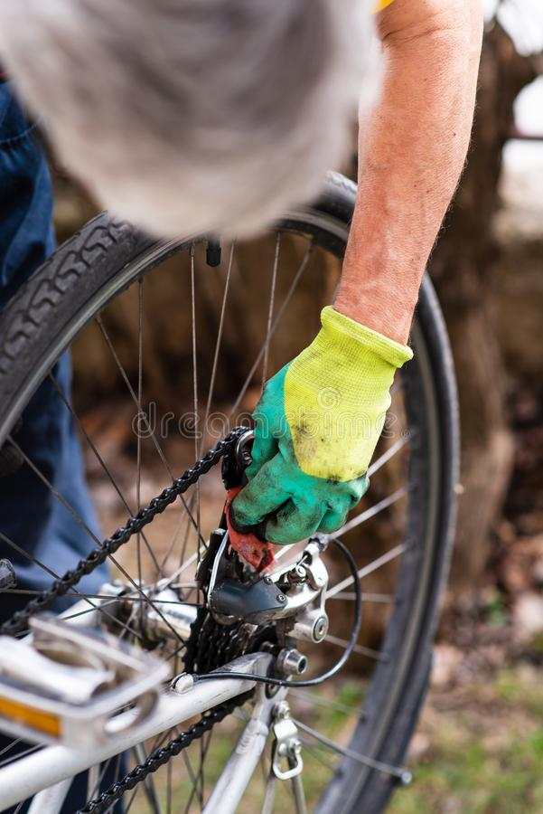 Man maintaining his bicycle for the new season. Man maintaining his bicycle for the new driving season, clean, cleaning, derailleur, male, drive, fix, fixing stock image