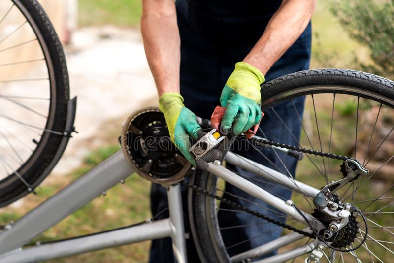 Man maintaining his bicycle for the new season. Man maintaining his bicycle for the new driving season clean cleaning pedal male drive fix fixing maintenance royalty free stock image
