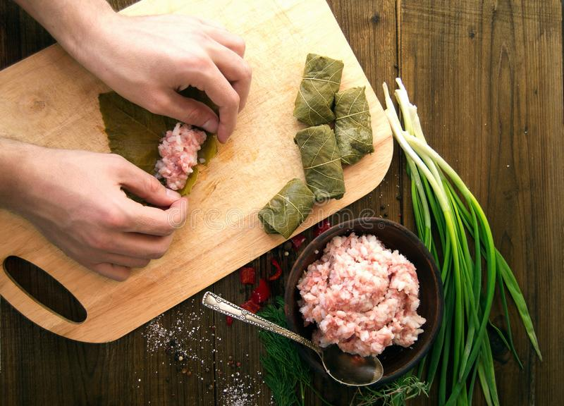 Man make a dish dolma rice with meat wrapped in grape leaves stock images