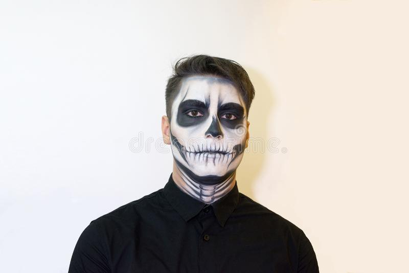 Man in make-up Halloween. drawing a vampire, skeleton on his face. Close-up photo. Man in make-up Halloween. drawing a vampire, skeleton on his face. Close-up royalty free stock photos