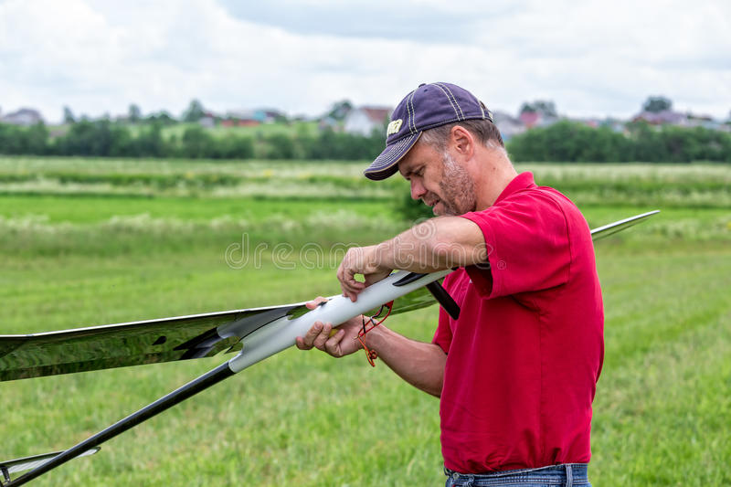 Man makes the assembly RC glider. Closeup stock photos