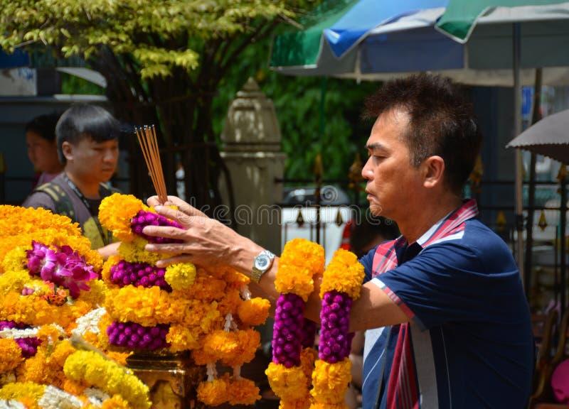 Man Makes Offering at Erawan Hindu Shrine in Bangkok. stock photography