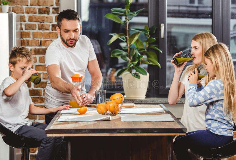 Man makes orange juice. Young men makes orange juice for his family for breakfast stock photos