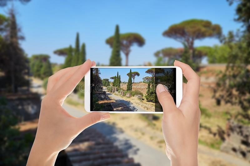 A man makes a photo of Pompeii. A man is making a photo of the road between ruins in Pompeii on a summer sunny day on a mobile phone royalty free stock photo