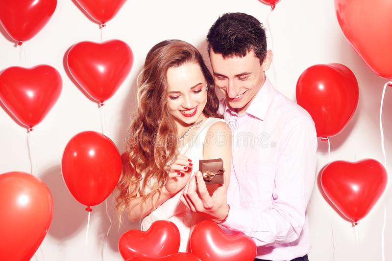 Man makes present to his lovely sweetheart girl. Lover`s valentine day. Valentine Couple. Boy gives to his girlfriend jewelry. Wedding ring. Propose background royalty free stock images