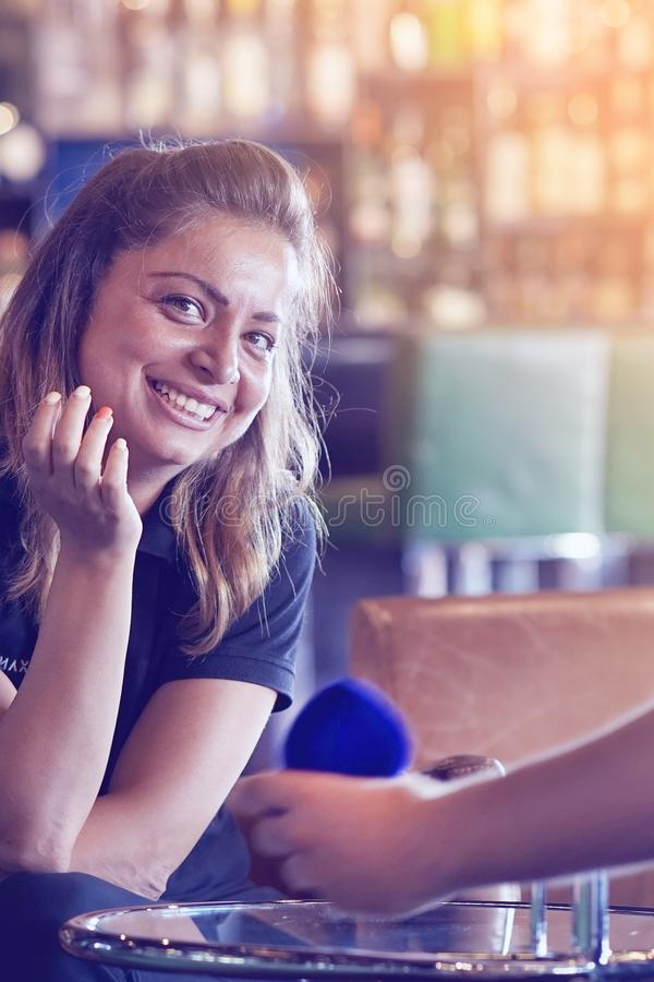 A man makes a proposal to marry the waitress at the bar. Hand man proposing to woman girlfriend to marry, engagement ring box. Lady hesitating, having doubt stock photography