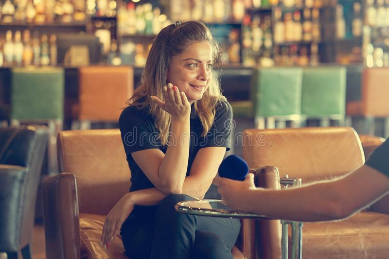 A man makes a proposal to marry the waitress at the bar. Young man proposing to waitress girlfriend to marry. Lady hesitating, having doubt, reluctant, thinkin royalty free stock photography