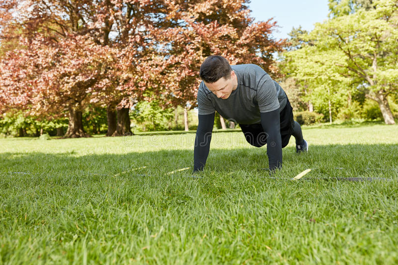 Man makes push ups at the park. In summer as bodybulding exercise stock photography