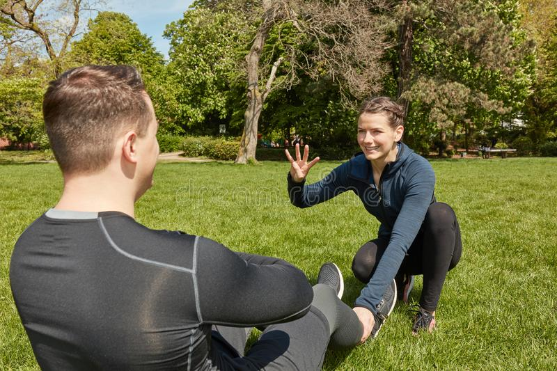 Man makes sit-ups with Personal Trainer. Man makes sit-ups with motivation from Personal Trainer royalty free stock image