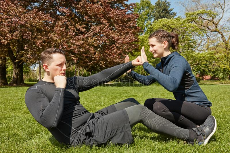 Man makes sit-ups with Personal fitness Trainer. At the park royalty free stock photos