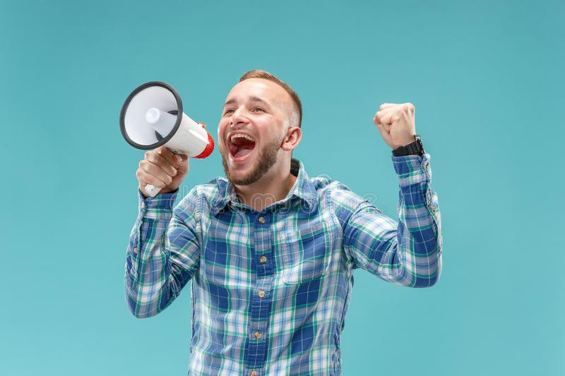 Man making announcement with megaphone. At blue studio background royalty free stock images