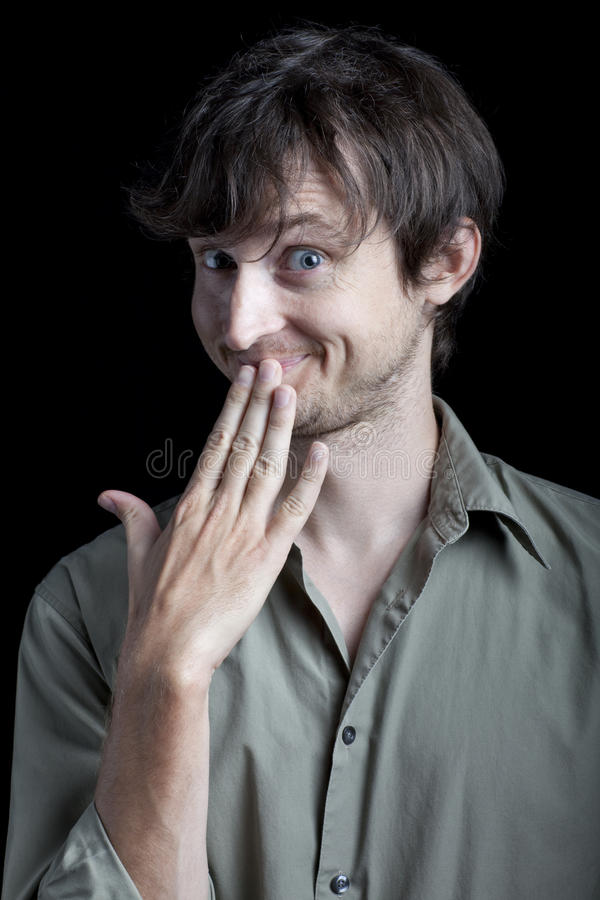 A man making a coy expression. A man looking surprised with wide eyes and open mouth. Photographed in front of a black backdrop stock photo