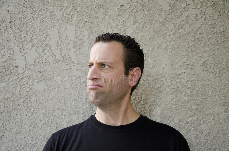 Man making a disgruntled face looking to the left. stock images