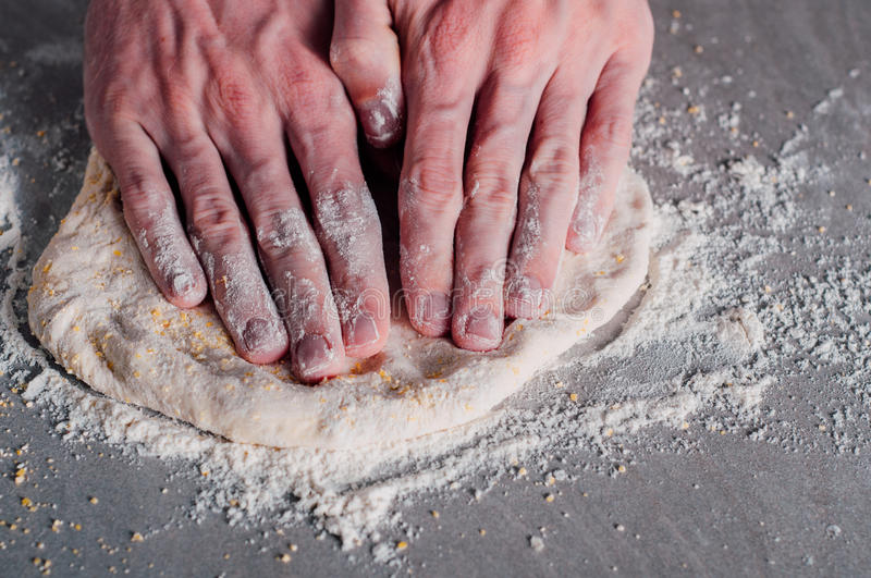 Man making dough for pizza. Man chef making dough for pizza Margherita royalty free stock image