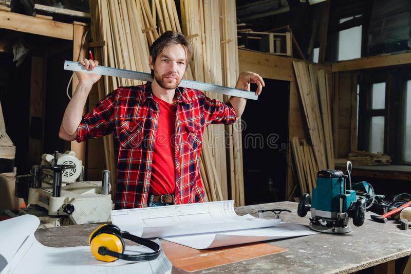 Man making draft plan using pencil on the table with workshop on background. stock images