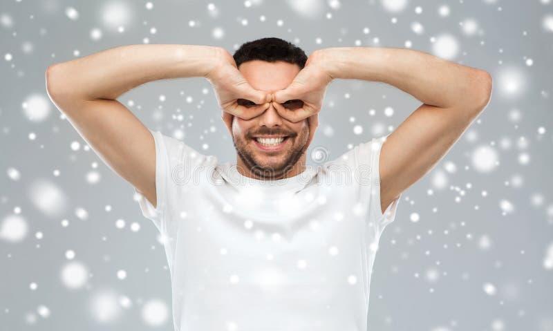 Man making finger glasses over snow stock images