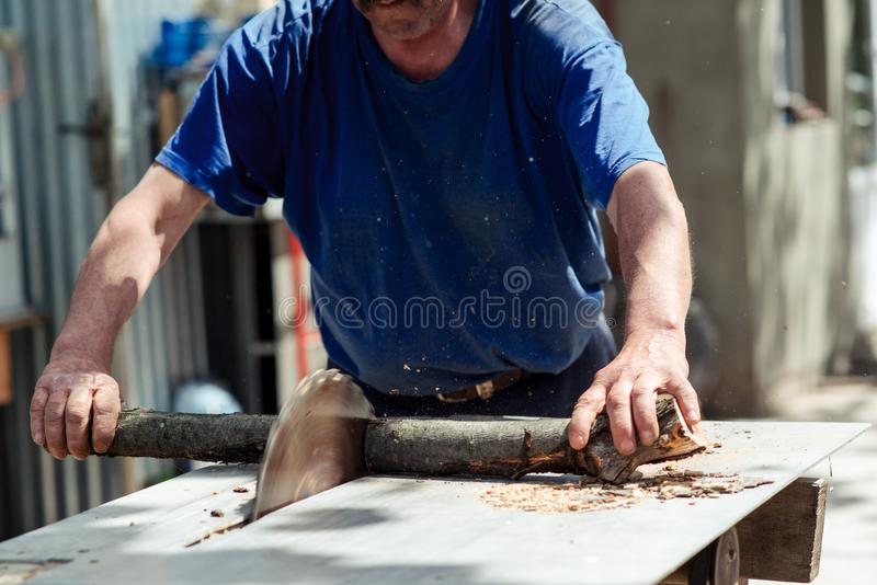 Man making firewood with buzz saw in the yard of a private house. royalty free stock photography