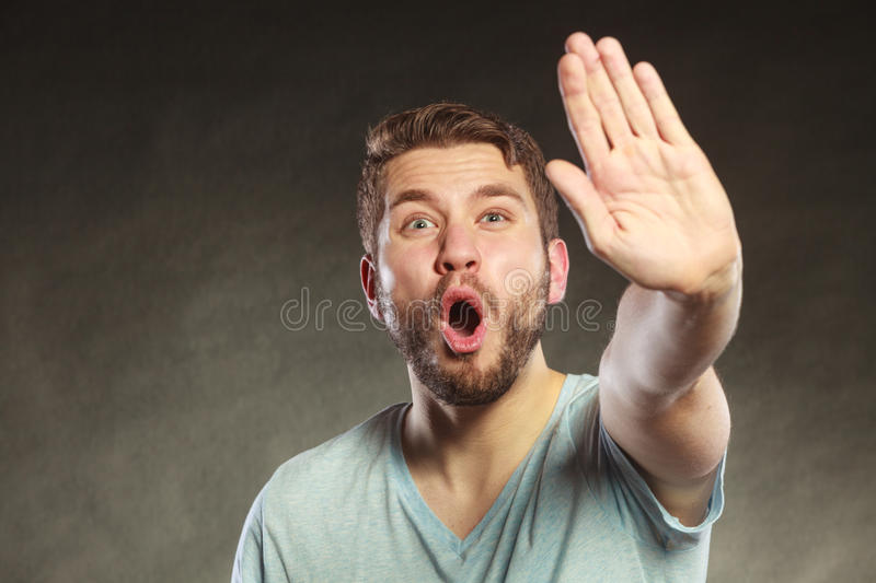 Man making hand stop gesture. Man give stop hand sign gesture. Facial expression open mouth black background royalty free stock image