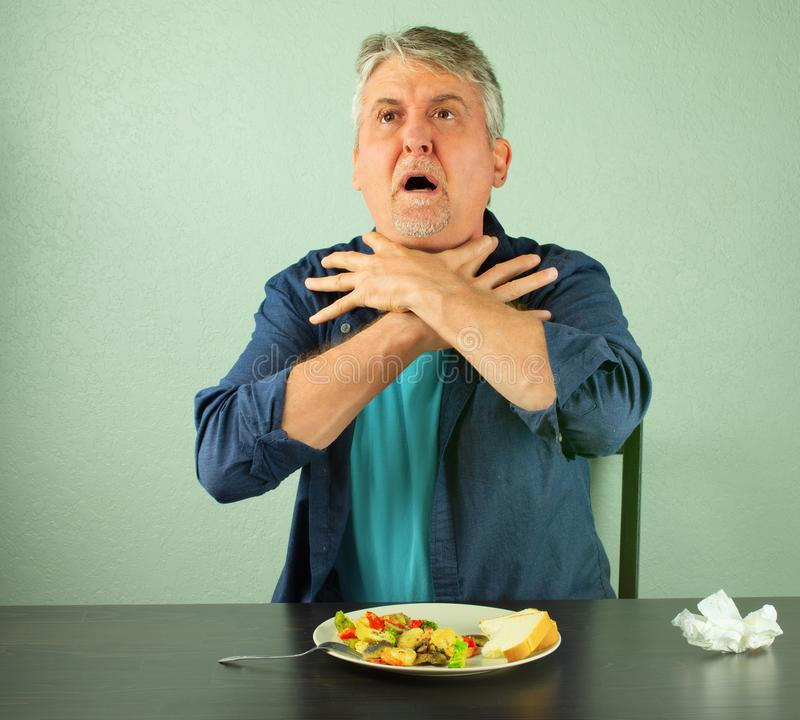 Man making the international sign for `I`m choking` as he chokes on food. A man is panicking and is in trouble as he chokes on food and is making the official stock photos