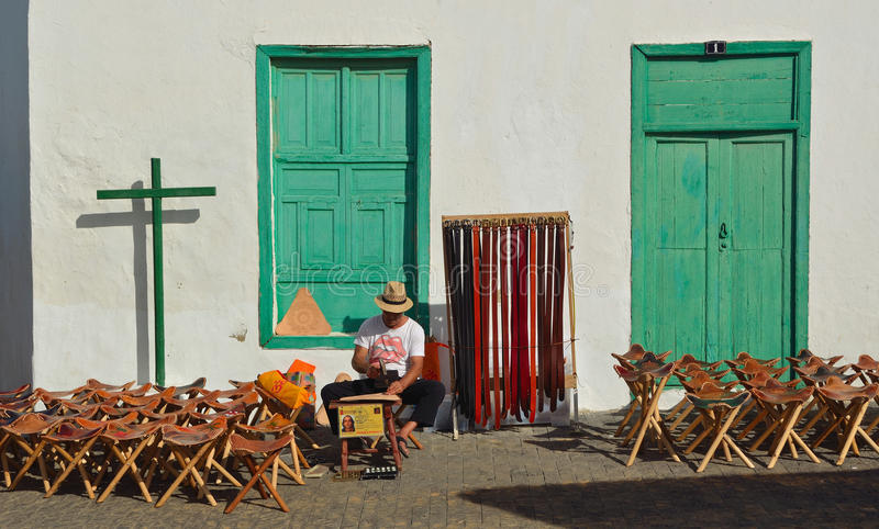Man making leather goods sitting with stools and belts for sale in front of old building. stock images