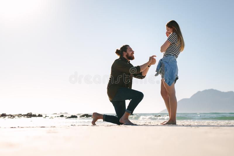 Man making a marriage proposal to woman at beach stock images