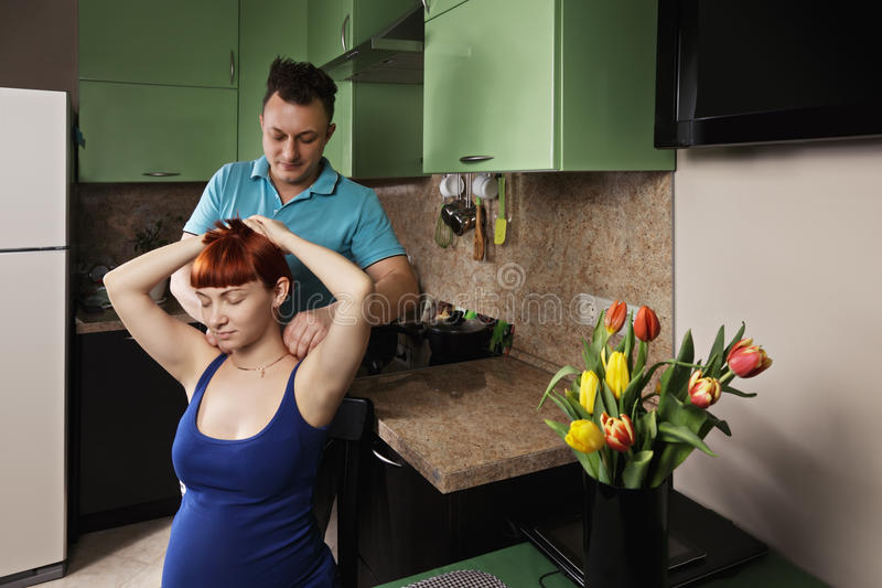 Man making neck massage. To pregnant women at the kitchen royalty free stock image