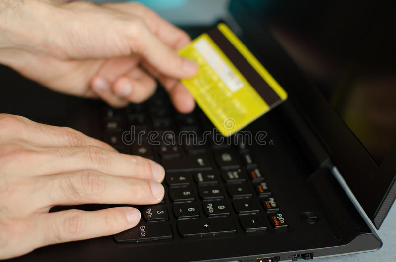 Man making an online purchase. Man holds credit card, as he makes an online purchase using his laptop royalty free stock photo