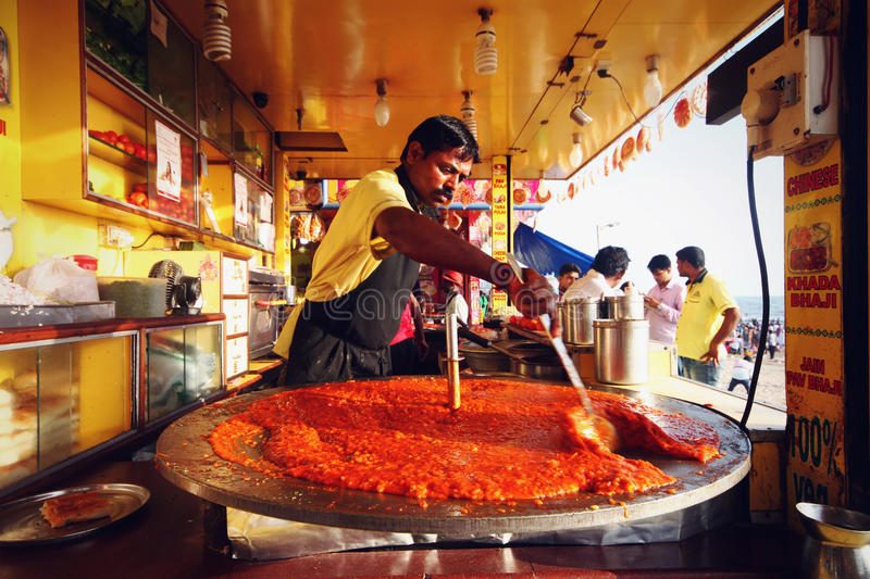 Man making Pao Bhaji in a giant pan at Juhu Beach, India. Pao bhaji is one of the most popular street foods of Western India