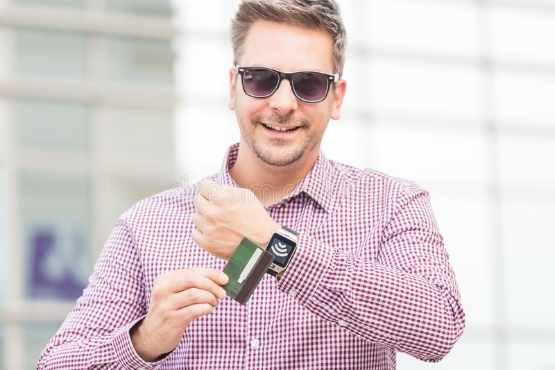 Man making payment by using smartwatch and debit card outdoors. Businessman using wireless payment system with credit card and smart watch in front of business stock photos
