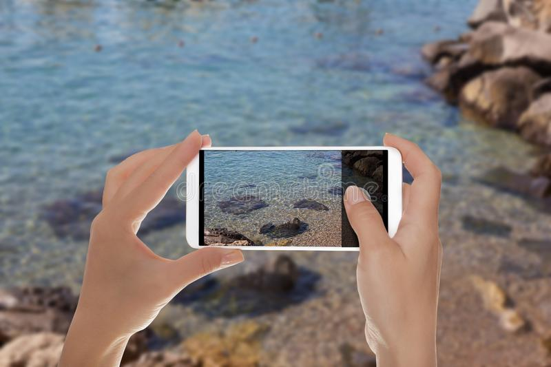 A man is making a photo of Amalfi shingle beach. A tourist is taking a photo of a small part of shingle beach with clear water on the Amalfi coast on a mobile royalty free stock photos