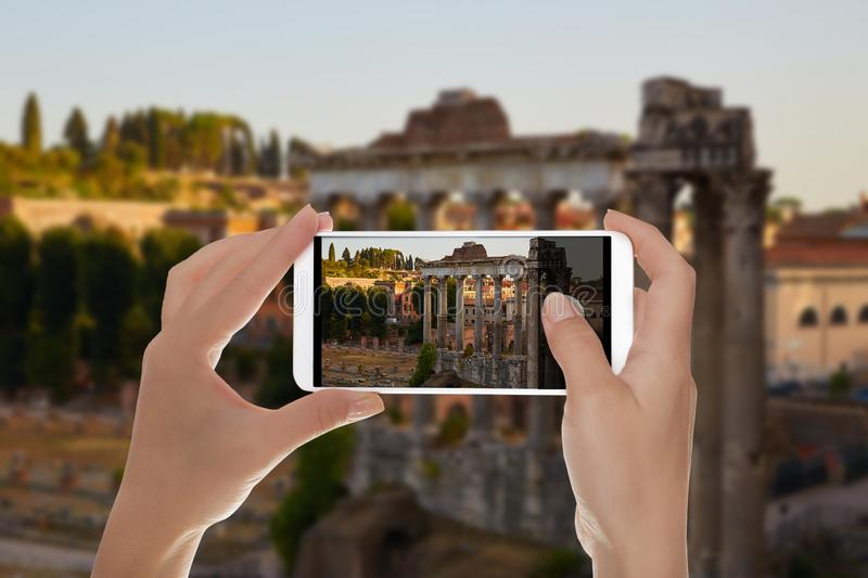 A man shooting Roman Forum. A man is making a photo of roman forum. Columns of the temple of Saturn in the evening. Rome, Italy on a mobile phone stock image