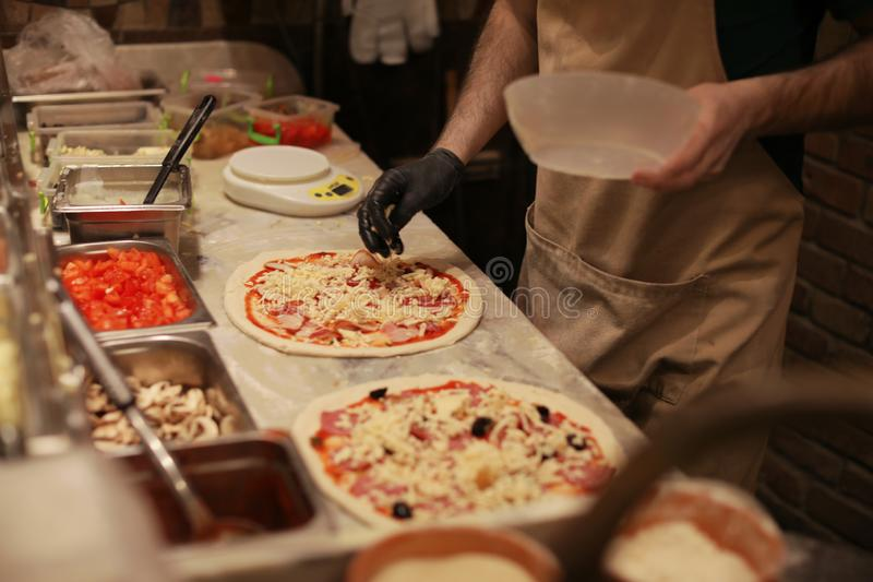 Man making pizzas at table. Closeup view royalty free stock photography