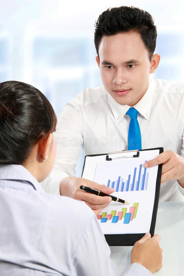 Man making a presentation and discussing bar chart. Business men and women making a presentation and discussing bar chart stock image