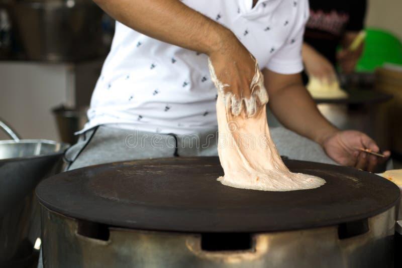Man making a Roti dough sheet. On a hot pan stock photos