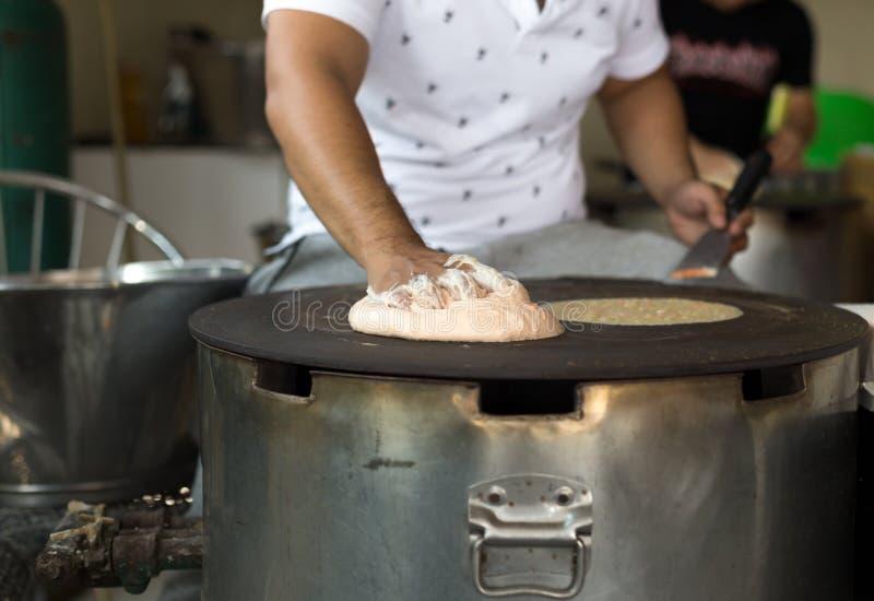 Man making a Roti dough sheet. On a hot pan stock photography