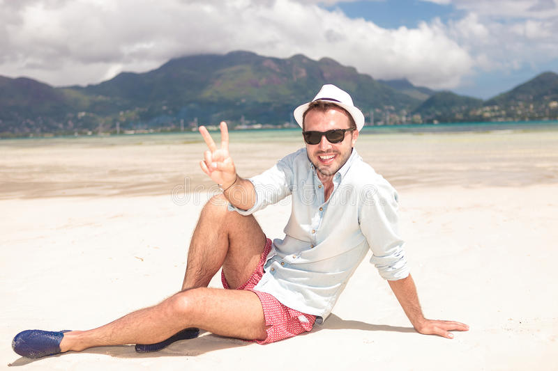 Man making the victory peace sign on the beach royalty free stock photos