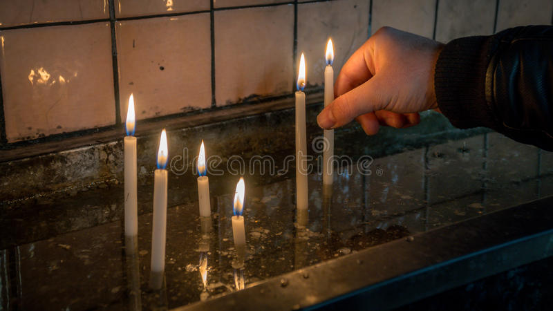 Man making a wish with sacred burning candles in church in Saint Antoine church in Taksim royalty free stock photo
