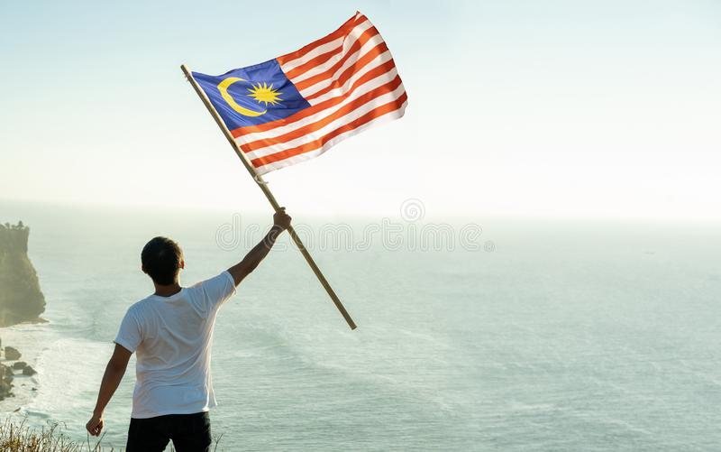 Man with malaysian flag of malaysia on top of the mountain. Asian man with malaysia flag standing proudly on top of hill royalty free stock photo