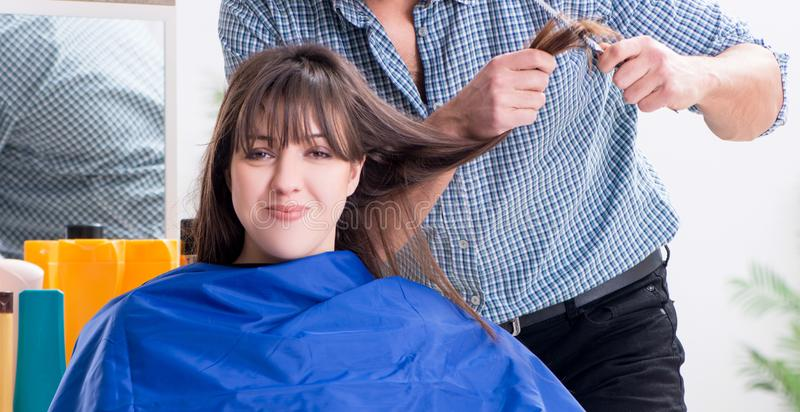 Man male hairdresser doing haircut for woman. The men male hairdresser doing haircut for woman stock images
