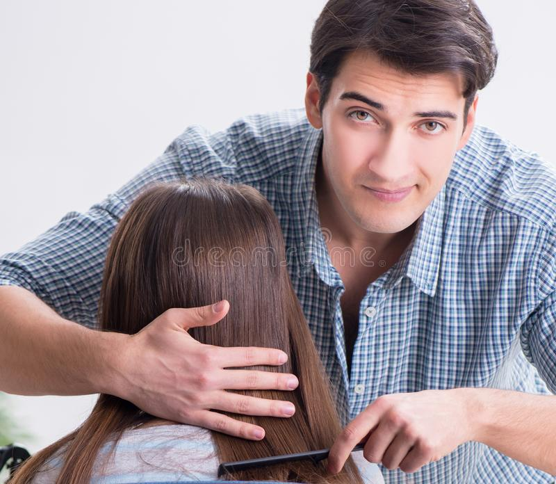 Man male hairdresser doing haircut for woman. The men male hairdresser doing haircut for woman royalty free stock images