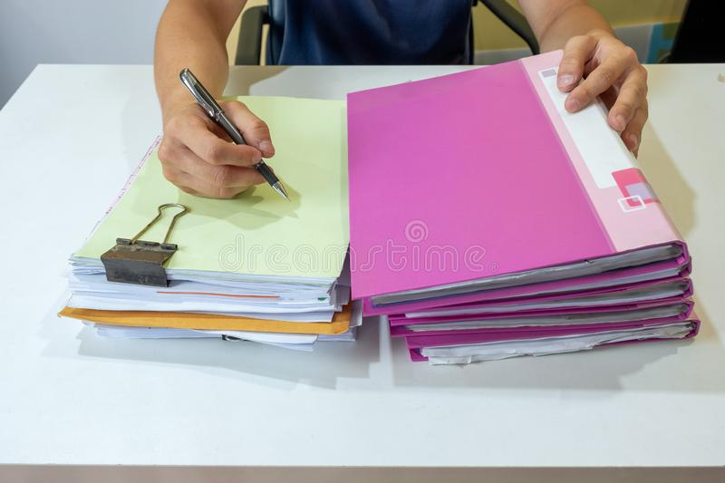 Man manager signing on accounting paper with stack file. On desk stock image